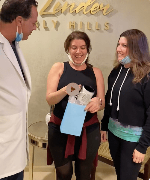 Woman in doctor's office with doctor, female companion, holding a blue goodie bag.