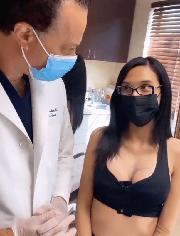 Woman wearing face mask and black sports bra next to doctor