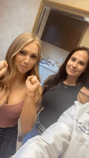 Pleased woman holding her fists up next to another woman in a doctor's office